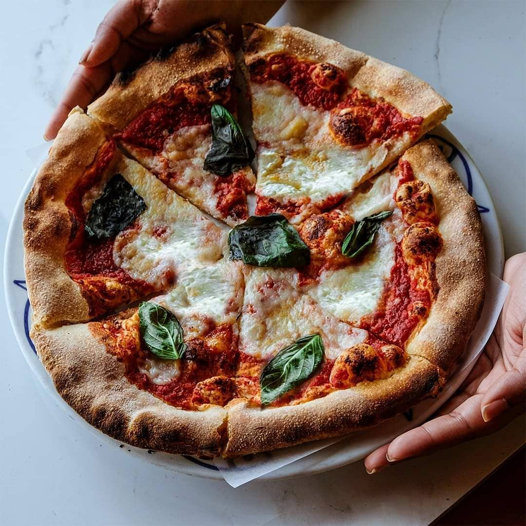 margherita pizza held in hands