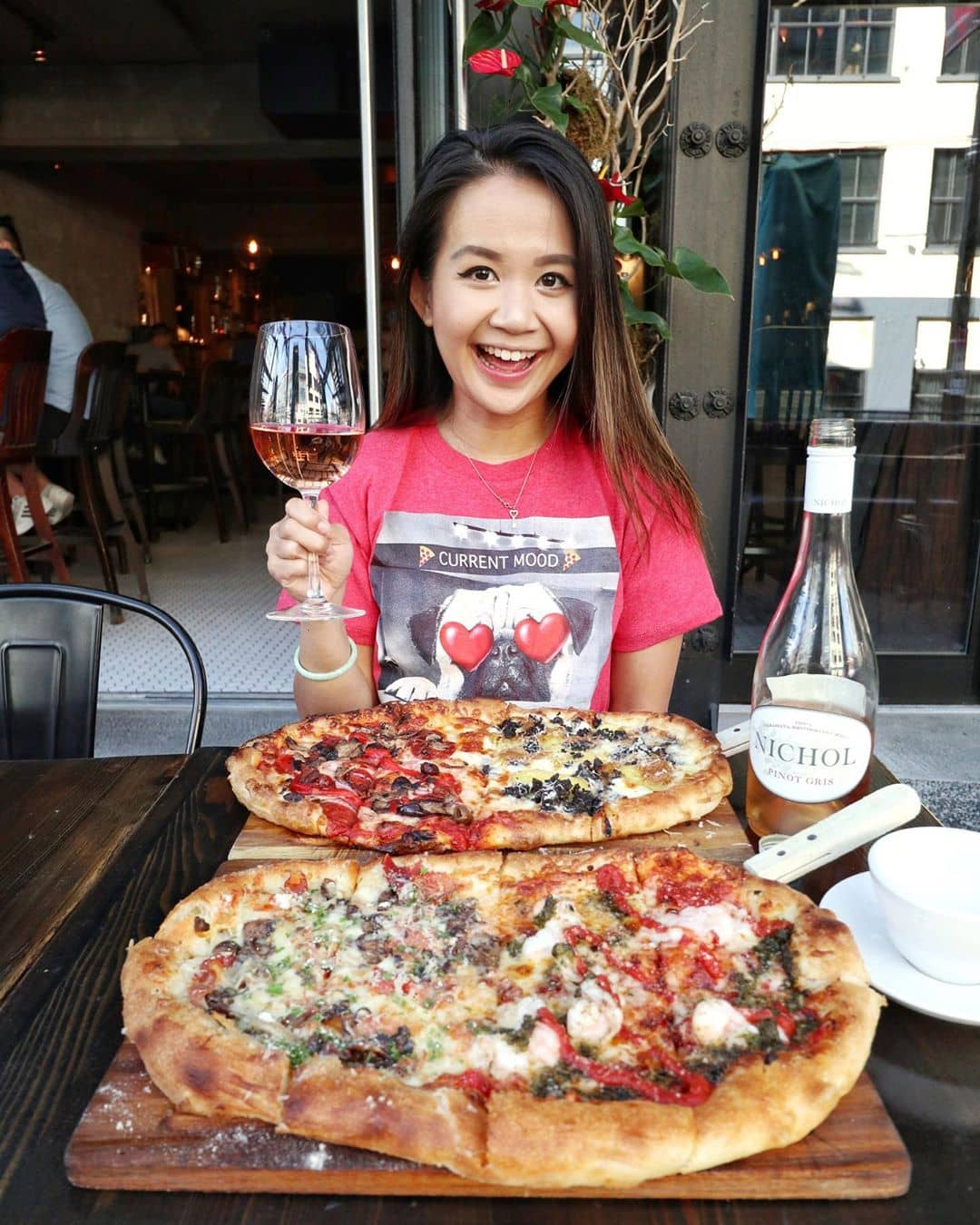 girl sitting infront of two pizzas holding a glass of wine