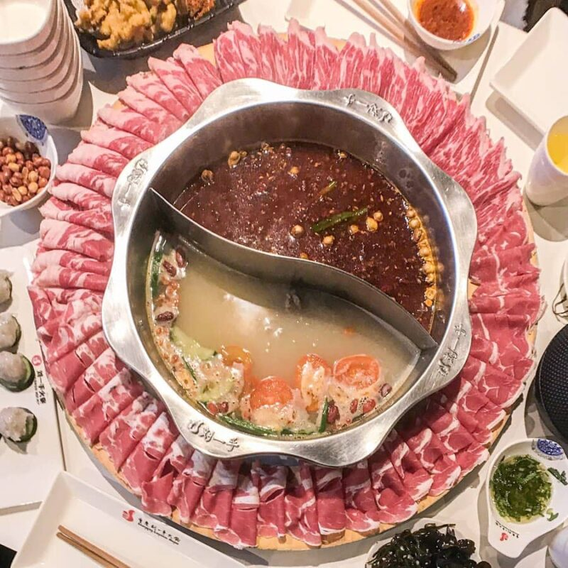 Hot pot in middle with two soup bases and ring of meat surrounding it