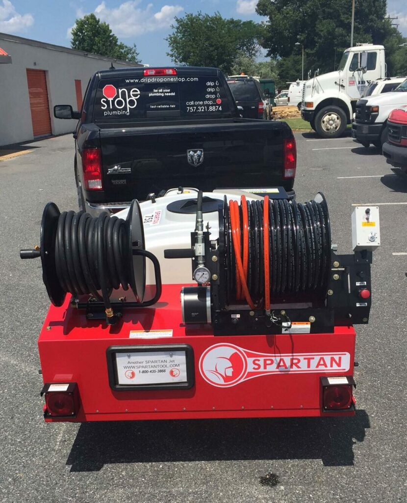 The Spartan Hydro Jetting machine in red towed by the One Stop Plumbing black pickup truck on the One Stop Plumbing Water Jetting page