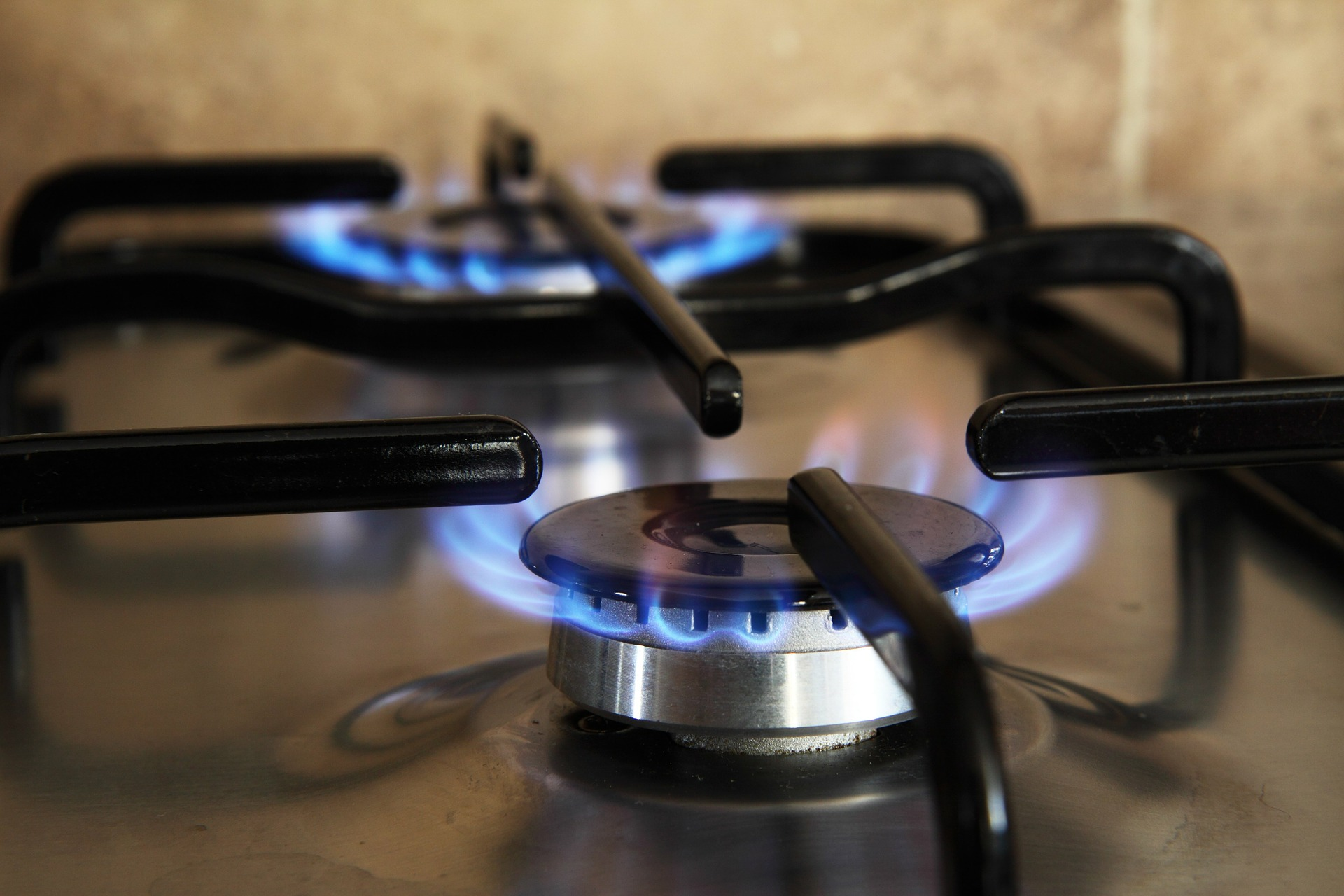 A gas appliance burner turned on in a black stovetop on the One Stop Plumbing gas appliances page