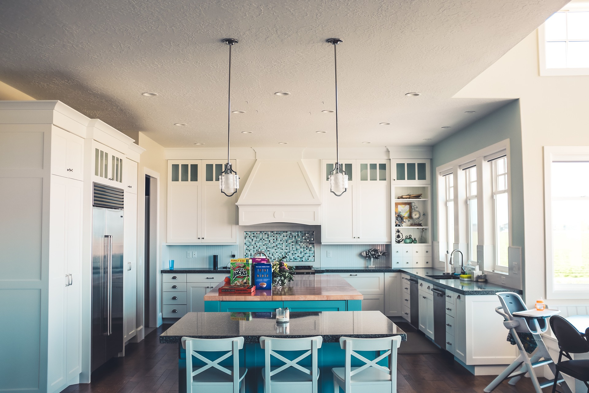 Remodeled kitchen in white and aqua blue with new appliances on the One Stop Plumbing page for Plumbing Remodeling