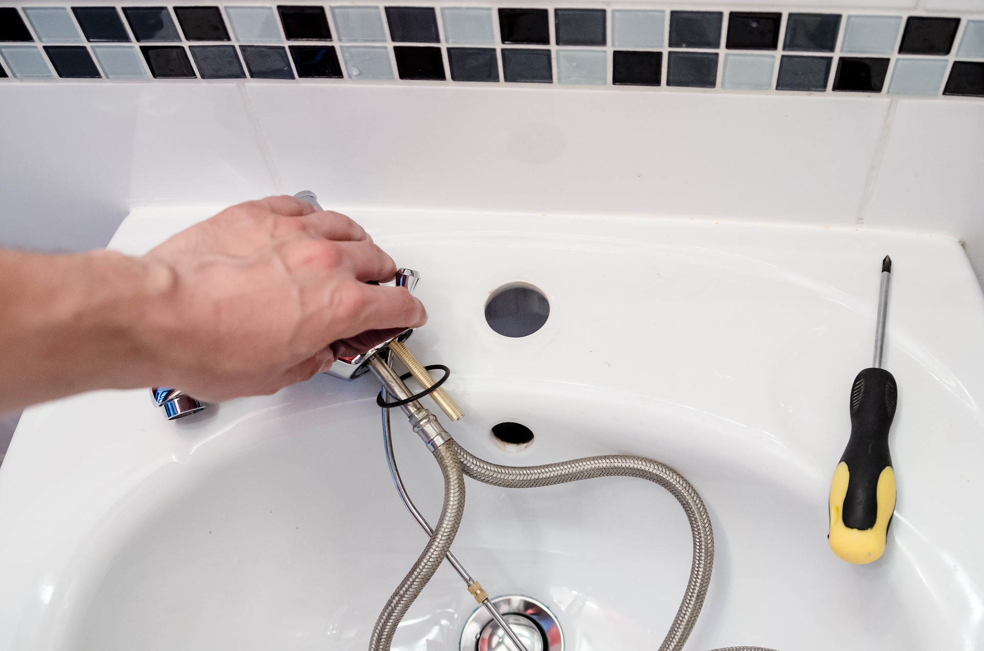 A white bathroom sink with the faucet taken out and a repair person's hands fixing the faucet and a yellow and black screwdriver on the One Stop Plumbing Faucets, Toilets & Sinks page