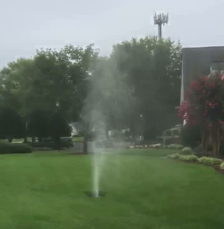 Water shooting up out of a hole in the ground with green grass and trees on the One Stop Plumbing Water Jetting page