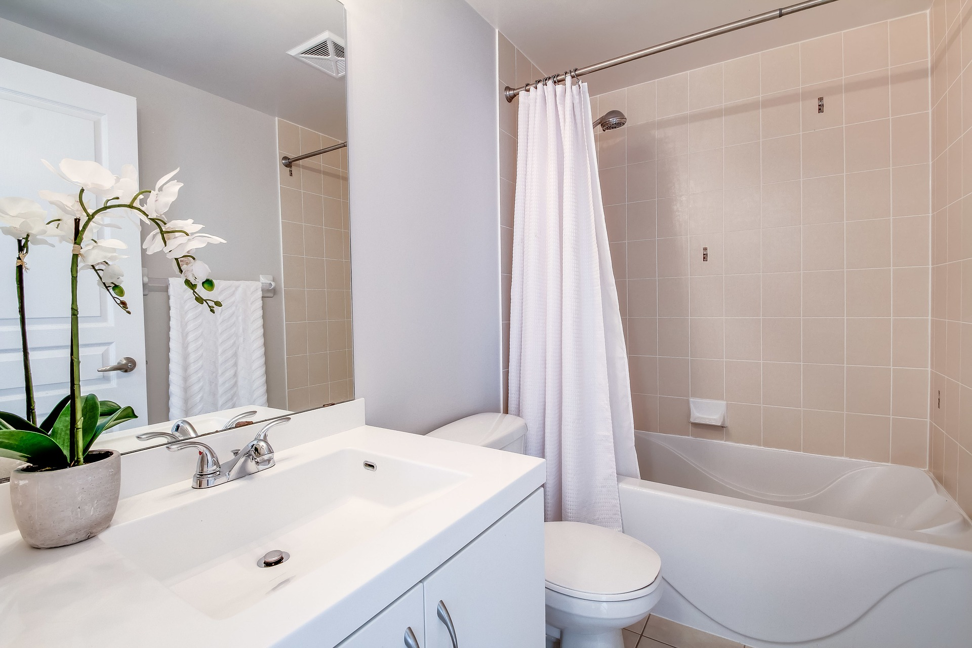 A white bathroom with sink, toilet, faucets and shower tub and brown tile with a flower on the counter on the One Stop Plumbing Faucets, Toilets & Sinks page