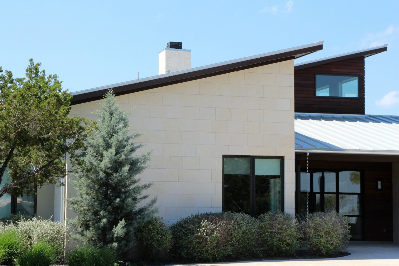 Austin limestone cladding panels are smooth white exterior stone panels on the exterior of a contemporary home