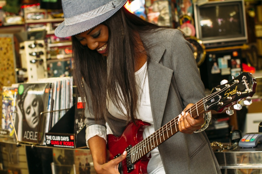 Women playing guitar and enjoying the effects of music in a record store. Photo by: unsplash.com