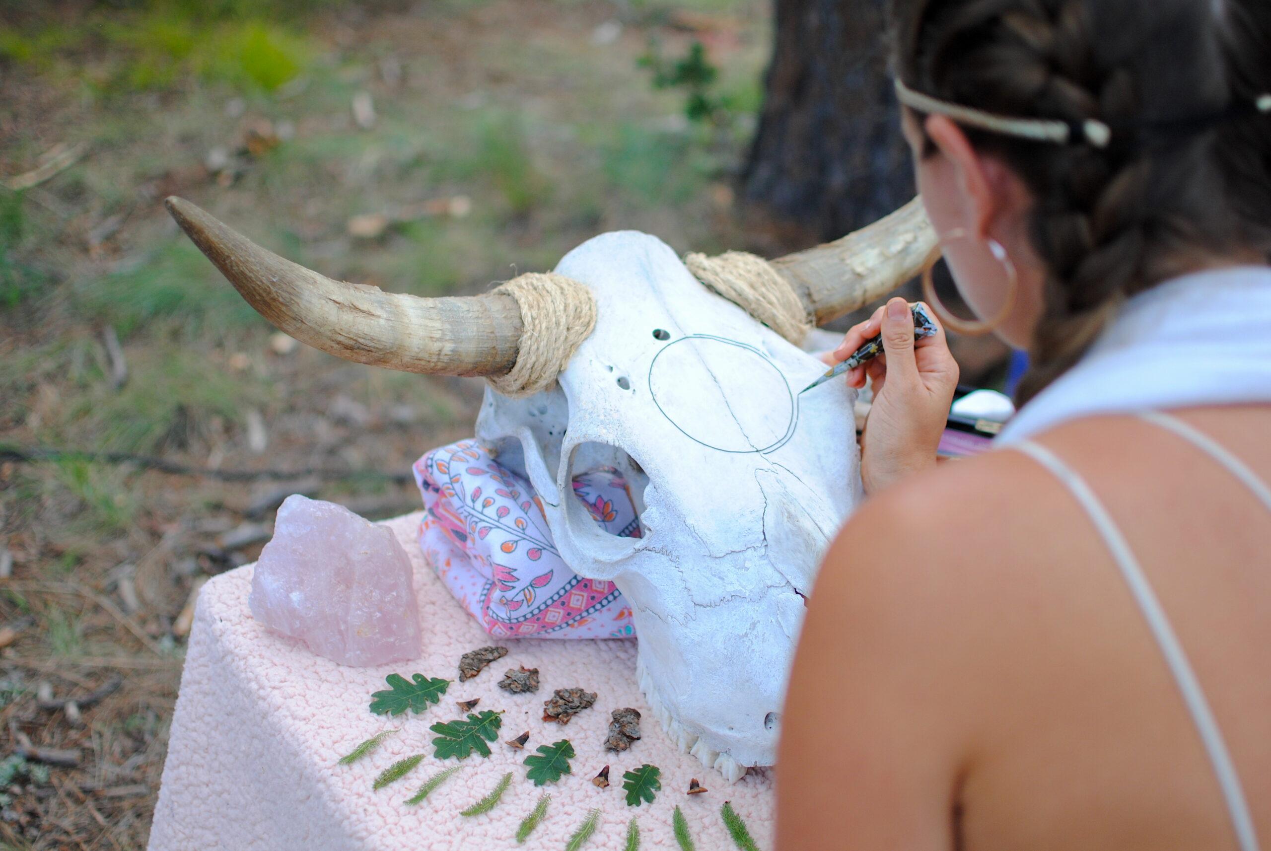A henna artist applies design to a cow skull during Rogue Reverie Soundbath. Photo by: Marissa Novel.