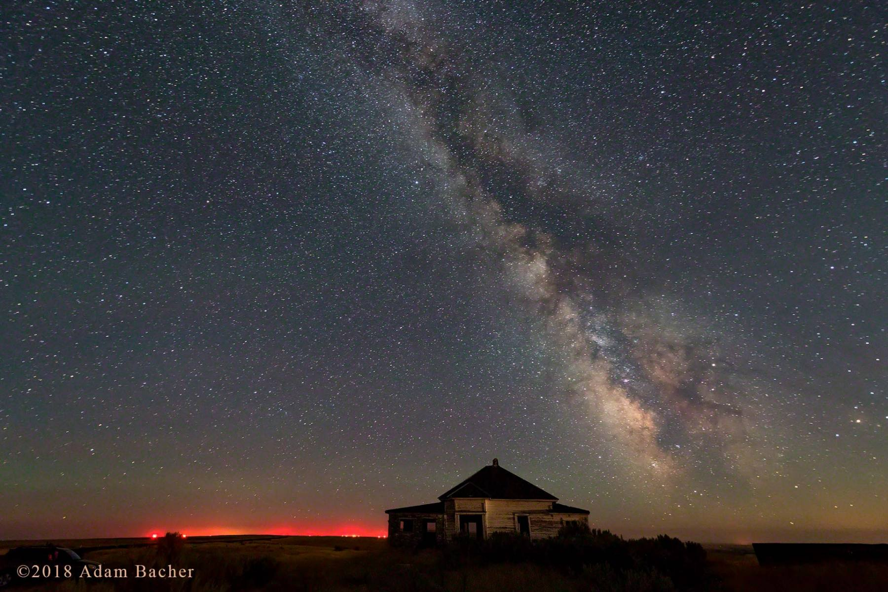 architecture of the universe: milky way night star photography, haunted house with red lights glowing in distance, oregon