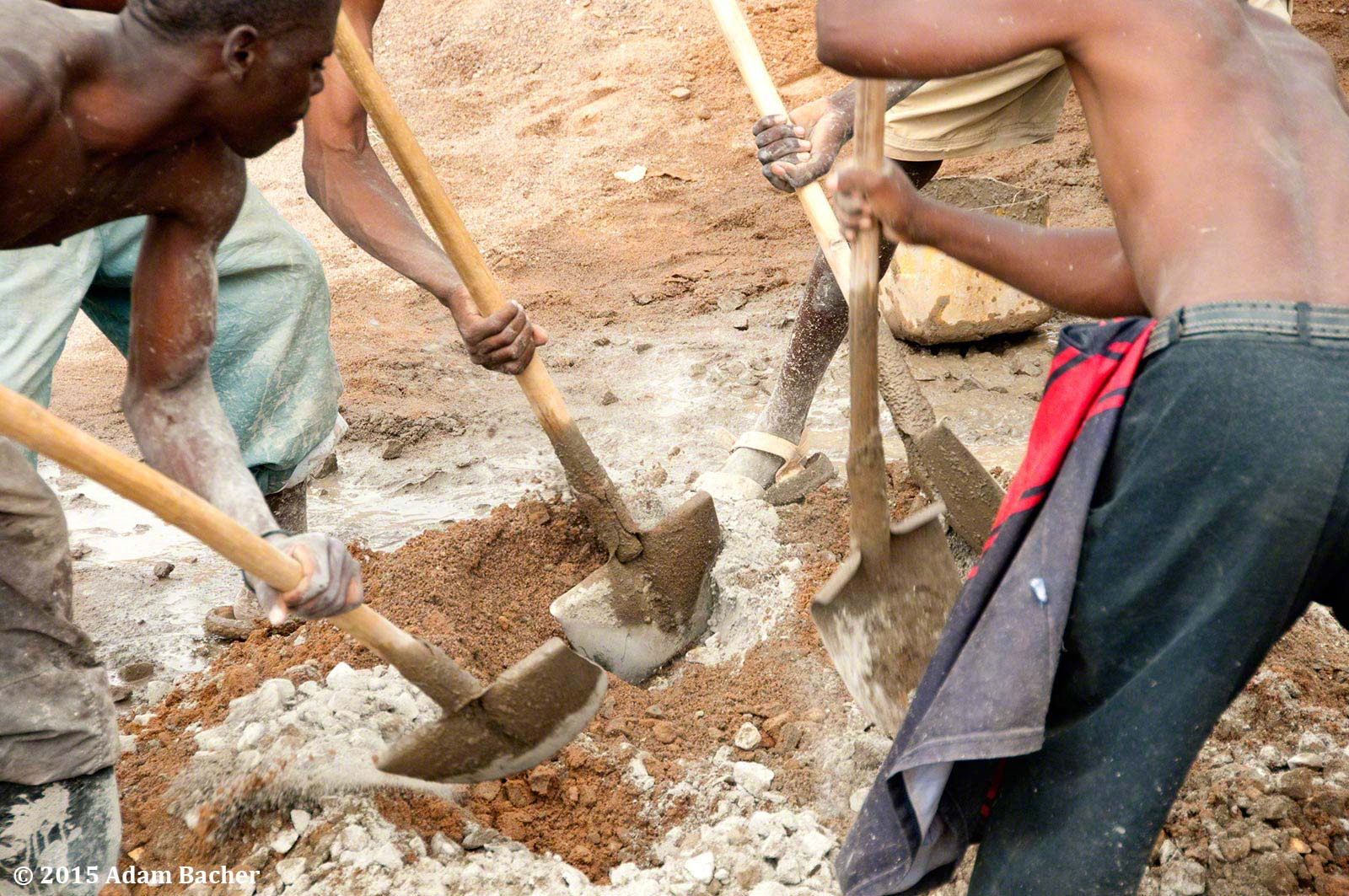 portland oregon editorial photographer in rwanda -workers shoveling cement