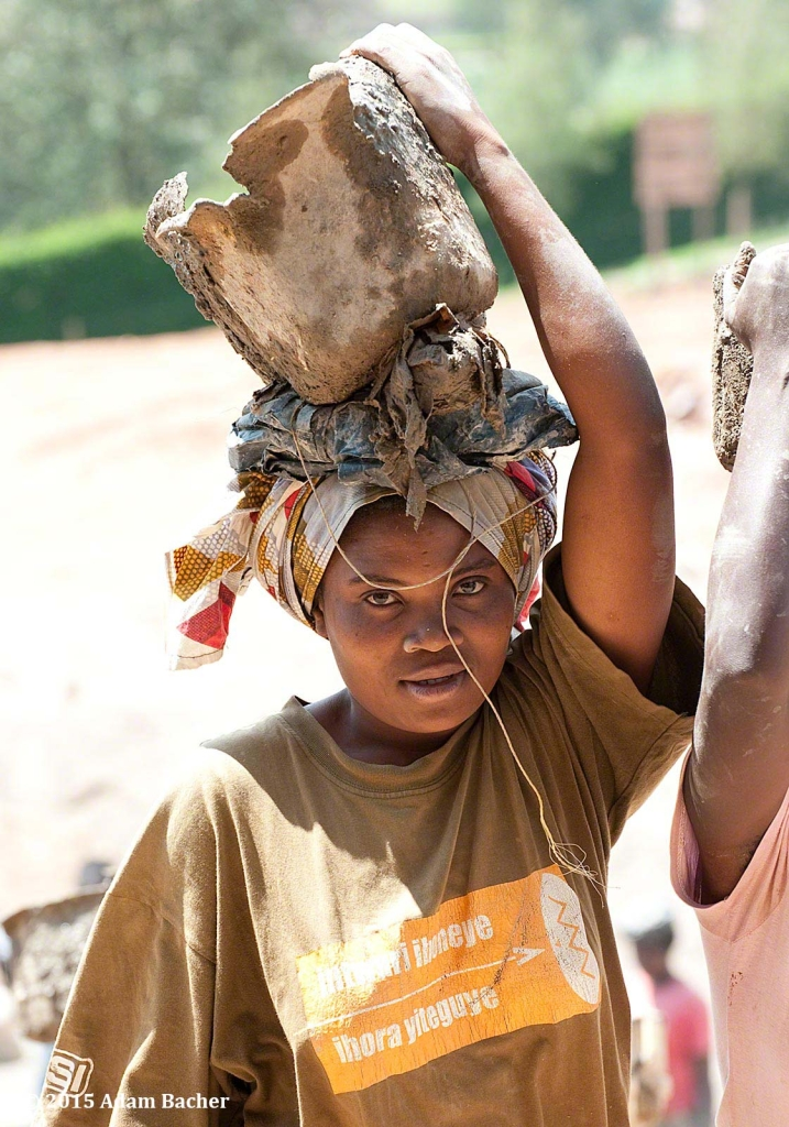 portland oregon editorial photographer - rwandan woman with bucket of cement