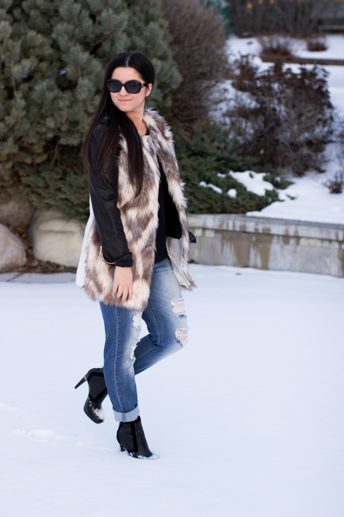styling a faux fur vest, faux leather jacket, red handbag, ripped jeans, boyfriend jeans, casual outfit idea, winter outfit, calvin klein