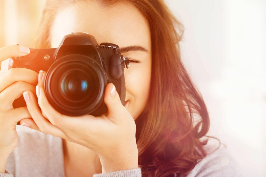 An image of a smiling woman holding a camera to her face preparing to take a photo.
