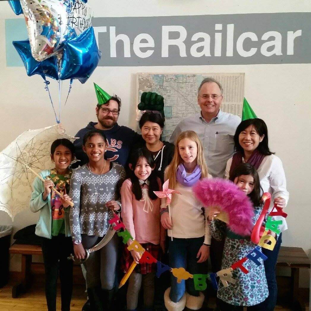 Escape room team adorning festive birthday accessories poses in front of The Railcar logo