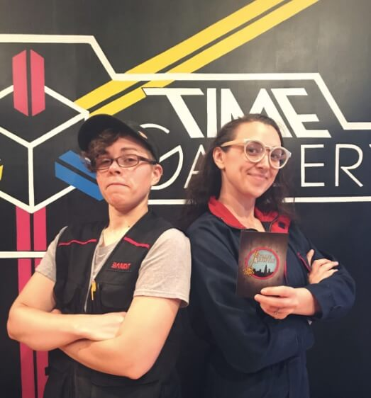 Escape Artistry Owner And Game Designer Pose In Front Of Time Gallery Logo