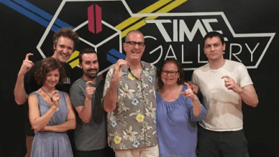 Escape Room Team Poses In Front Of Time Gallery Logo