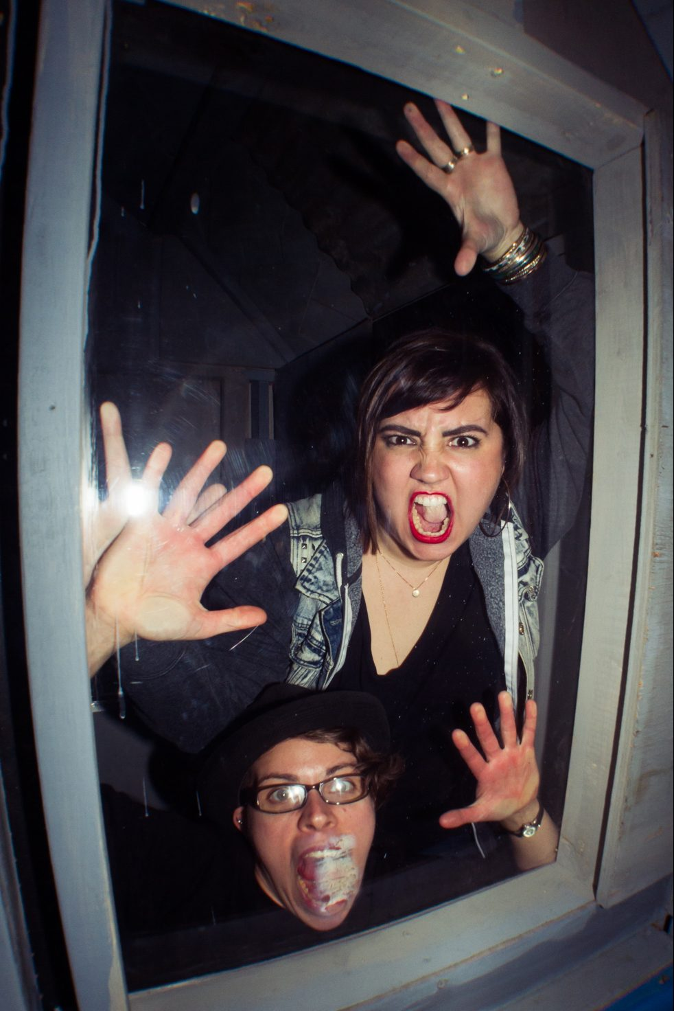 Two People With Yelling Faces Pressed Against A Window