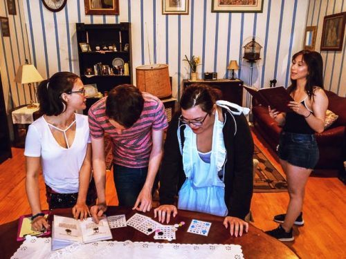 Three People Looking At Puzzles On A Table While Another Holds A Book