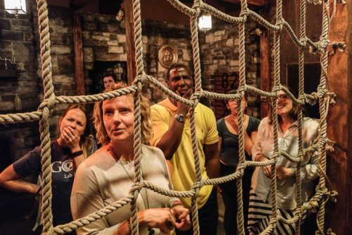 Group of people looking curiously through rope net
