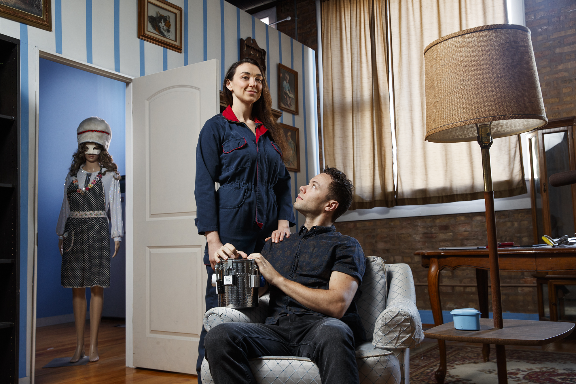 Gift Memories Tribune Photo Shoot . Woman In Blue Jumpsuit Looking At Camera While A Man Sitting In A Chair Looks Up At Her.