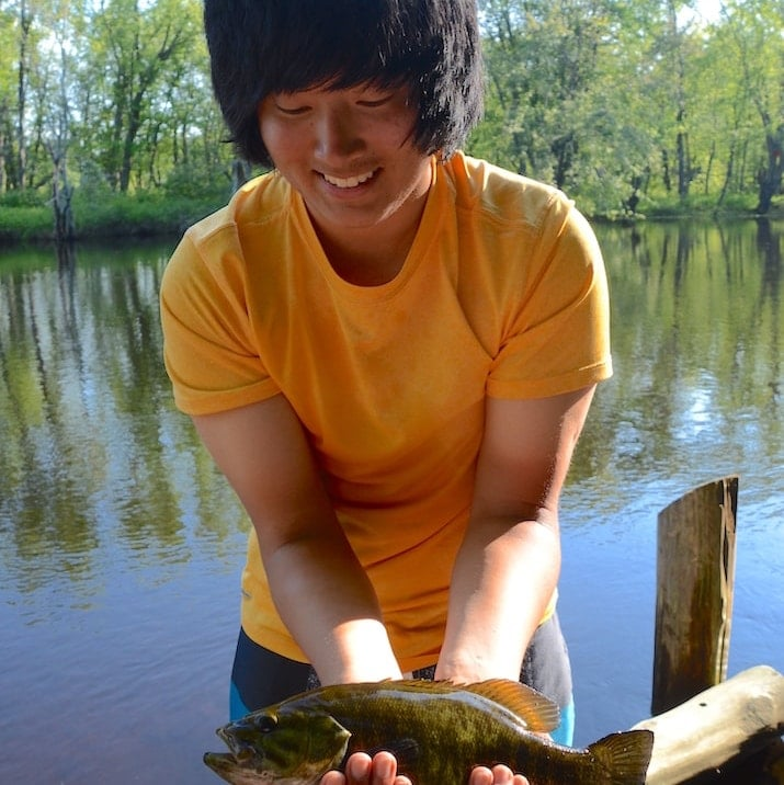 A young person holds a recently caught smallmouth bass