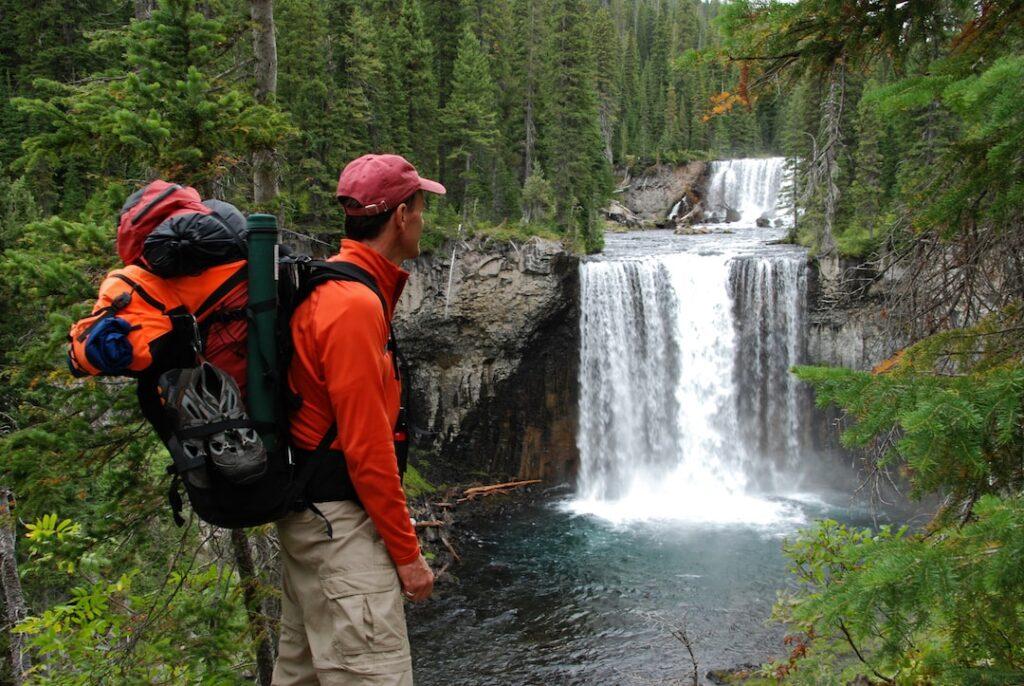 A backpacker in Yellowstone looks at a waterfall