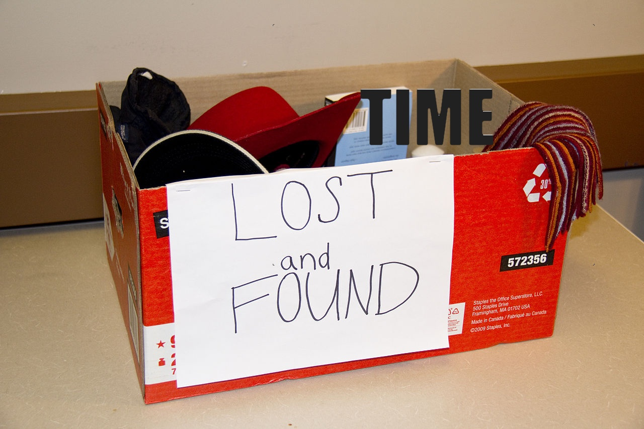 Image of a lost and found box with a hat, some other stuff, and the word time.