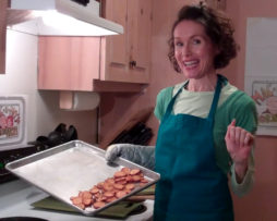 Health Coach, Mo the Morselist, in the kitchen holding a tray of baked sweet potato chips.