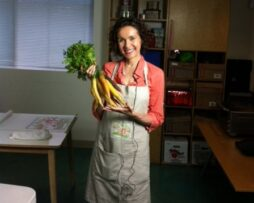 Health Coach, Mo The Morselist, posing in a salmon colored top and beige apron while holding a bunch of carrots.