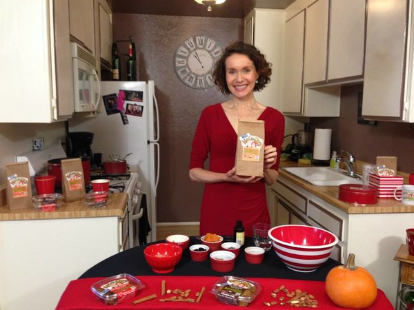 Health coach and Recipe Developer, Mo The Morselist, standing in a kitchen in a red dress while smiling and holding a bag of her Morselicious baking and cooking mix. Before her is a table decorated I red with various shaped bowls full of recipe ingredients.
