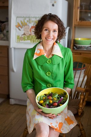 Certified Health Coach, Mo The Morselist, is sitting in a chair in a kitchen in an orange and yellow dress beneath a bright green jacket and posing with a green bowl of a rainbow of vegetables.