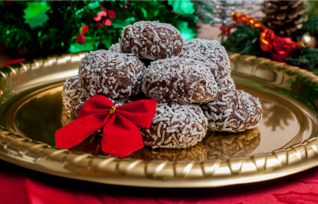 Minty cocoa balls piled on a gold plate with a red bow.