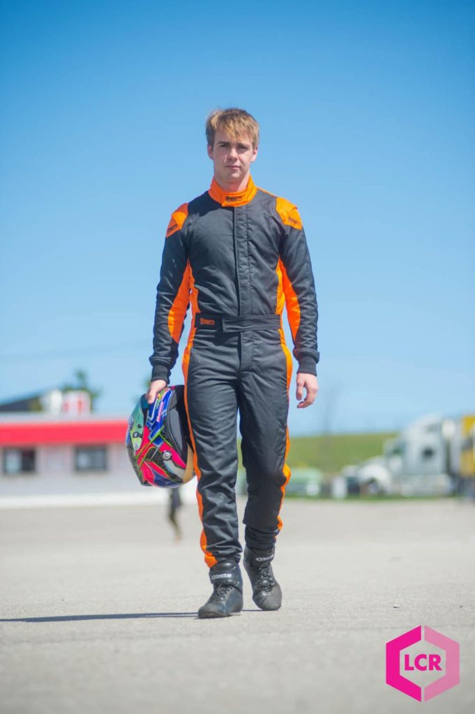 Logan Cusson in his racing suit walking with helmet in hand