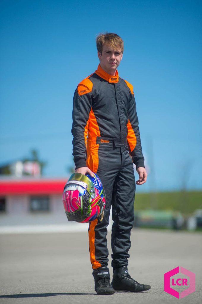 Logan Cusson holding racing helmet at Mosport