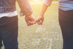 Close-up of loving couple holding hands while walking outdoor, Couple in love concept.