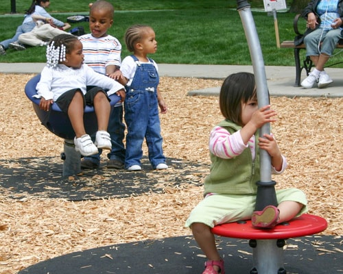Engineered wood fiber safety surfacing at pre-school age playground equipment by KOMPAN