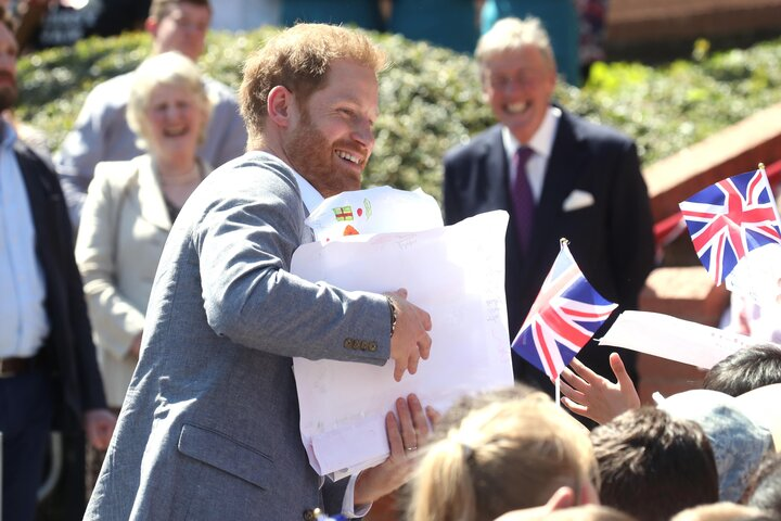 The Duke of Sussex receives gifts from well-wishers as he arrives for a visit to the Barton Neighbourhood Centre