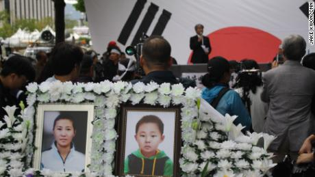 Photos of Han Sung-ok and Kim Dong-jin are displayed at a protest in Seoul after their deaths.