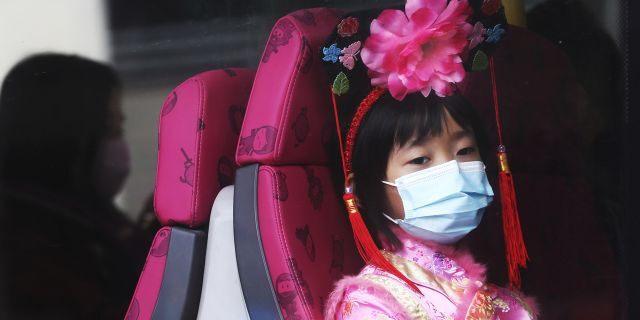 A girl wears a mask inside a bus in Hong Kong, Saturday, Jan. 25, 2020.