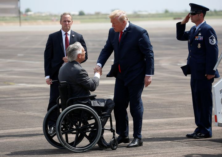 Gov. Greg Abbott, seen here greeting President Donald Trump in May 2018, appears to share Trump's concerns about refugees.