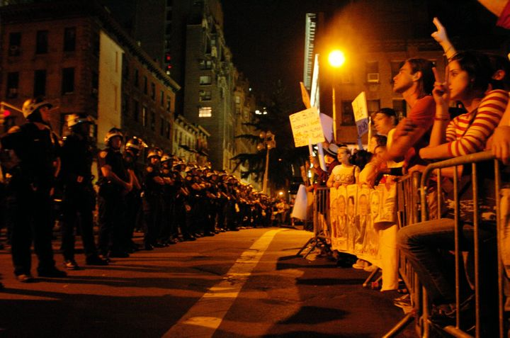 Police face protesters outside Madison Square Garden as then-President George W. Bush delivers his speech on the last day of