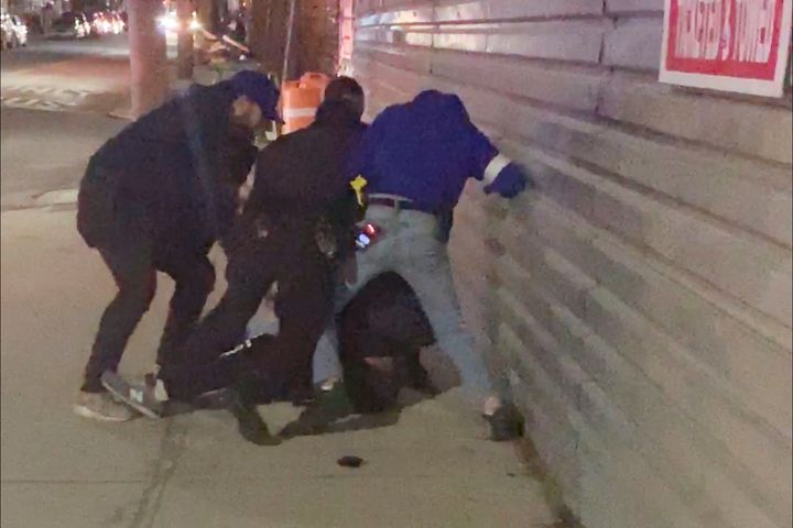 In this image made from video, New York City police officers forcefully arrest 20-year-old Fitzroy Gayle in the Brooklyn boro