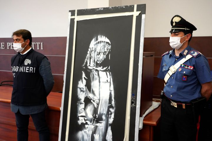 Italian authorities unveil a stolen artwork painted by Banksy as a tribute to the victims of the 2015 terror attacks at the B