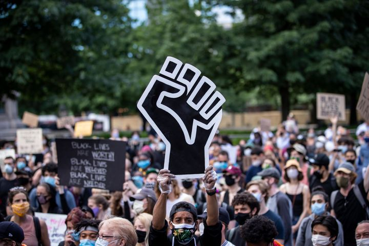 A protester wearing a mask holds a large Black power raised fist in the middle of a crowd that gathered at Columbus Circle on