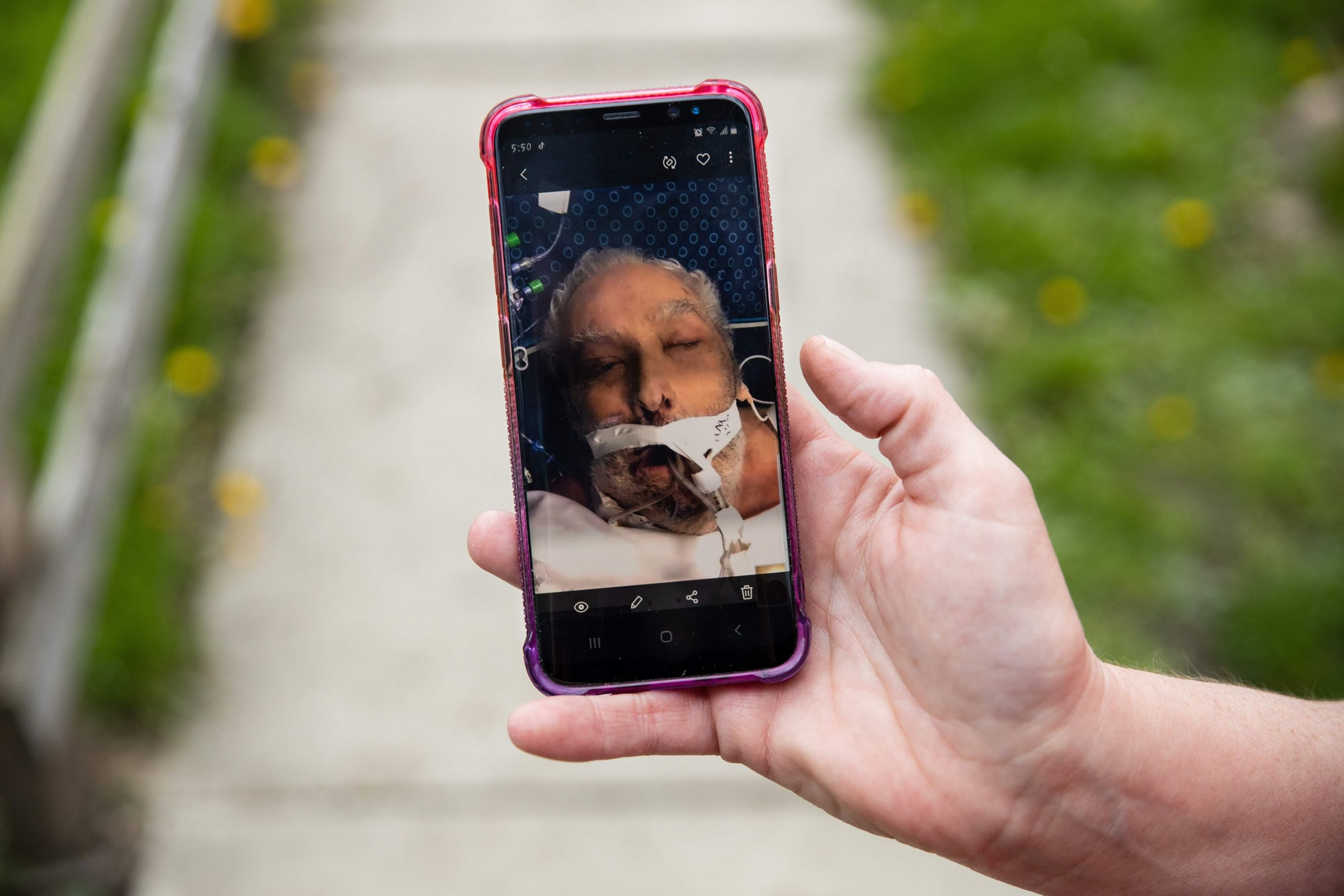Christine Bevington holds a photo of her stepfather, Jesse Zeigler, taken as his family said goodbye on a video call before h