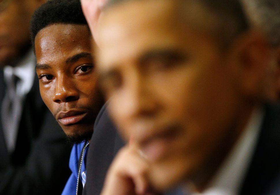 Youth leader Rasheen Aldridge of the Ferguson Commission listens asPresident Barack Obama speaks at the White House on