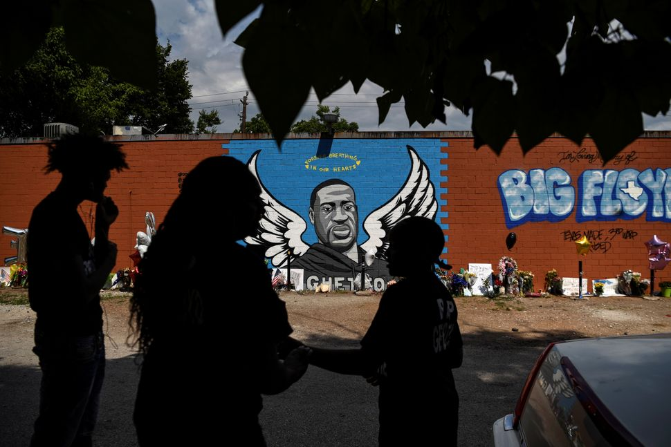 Mourners photograph a mural of George Floyd, whose death in Minneapolis police custody sparked nationwide protests against ra