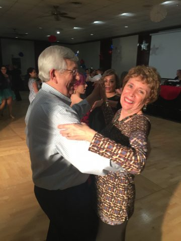 Happy senior lady dancing with her devoted husband.