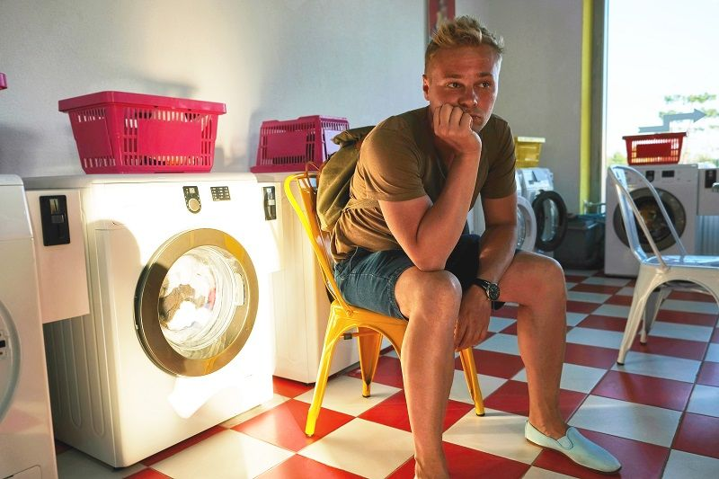 A-young-man-in-the-Laundromat-sits-on-a-chair-and-waits-for-the-completion-of-washing--cm