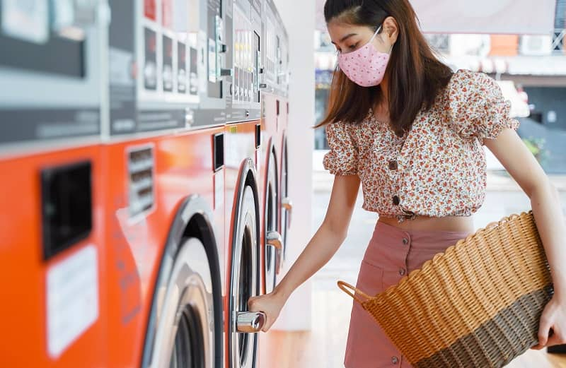 Young beautiful asian woman with mask doing laundry at laundromat shop during Covid-19 and coronavirus outbreak, New normal lifestyle concept-cm